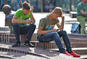 two boys use cell phones